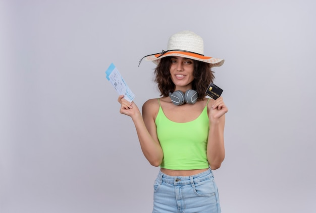 Une jeune femme heureuse aux cheveux courts en vert crop top portant chapeau de soleil montrant les billets d'avion et carte de crédit sur fond blanc