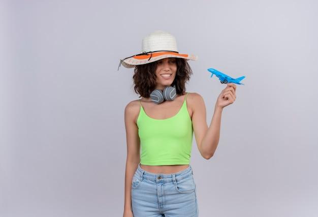 Une jeune femme heureuse aux cheveux courts en vert crop top portant un chapeau de soleil tenant un avion jouet bleu sur fond blanc