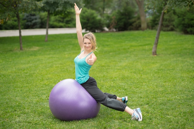 Jeune femme heureuse avec ballon de fitness, en plein air
