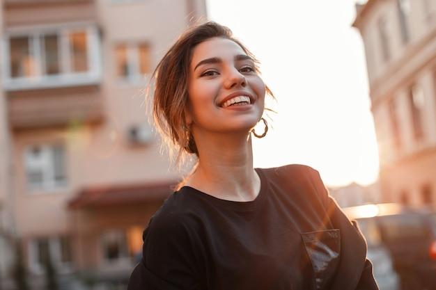Jeune femme heureuse avec un beau sourire dans un t-shirt élégant dans un manteau est debout et apprécie le coucher de soleil orange dans la ville près des maisons