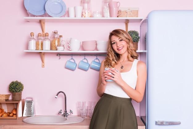 Jeune femme heureuse, boire du café ou du thé à la maison dans la cuisine. belle fille blonde prend son petit déjeuner avant d'aller au bureau. pause café. intérieur de cuisine moderne pastel rose et bleu