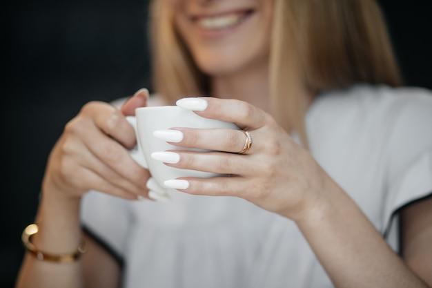 Jeune femme heureuse, boire du thé vert dans un café