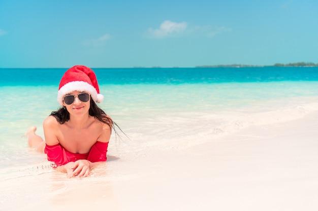 Jeune femme heureuse en bonnet de noel en maillot de bain sur une plage blanche en vacances de noël