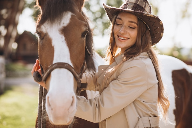Jeune femme heureuse avec cheval au ranch