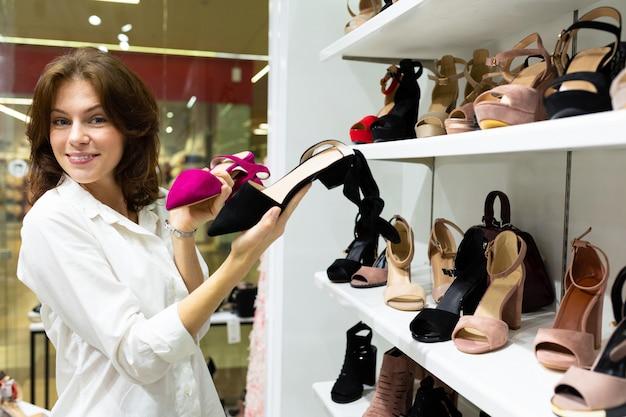 Jeune femme heureuse choisit entre des sandales en daim roses et noires en boutique