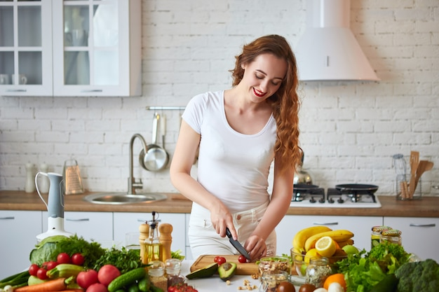 Jeune femme heureuse, couper les tomates pour faire de la salade dans la belle cuisine avec des ingrédients frais verts à l'intérieur. alimentation saine et concept de régime. perdre du poids