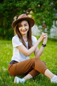 Jeune femme heureuse dans un chapeau est assise sur une pelouse verte dans un parc. une fille d'apparence européenne avec un sourire sur son visage par une belle journée d'été ensoleillée