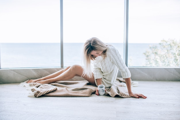 Jeune femme heureuse dans une robe tricotée blanche, profitant de la vue sur la mer à côté de la grande fenêtre avec une tasse de thé et de rire. fenêtre panoramique. revêtements de sol.