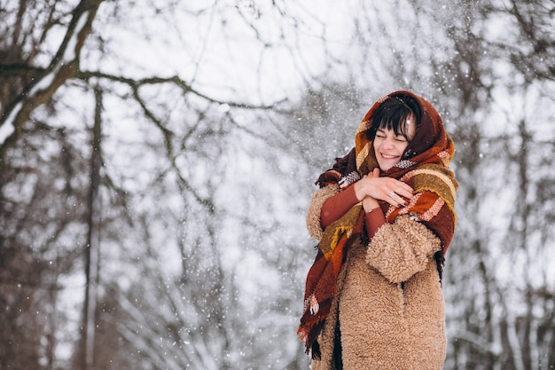 Jeune femme heureuse dans des vêtements chauds dans un parc d'hiver