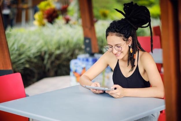 Jeune femme heureuse avec des dreadlocks lisant depuis sa tablette alors qu'il était assis à une table, souriant et pensant à quelque chose de positif.