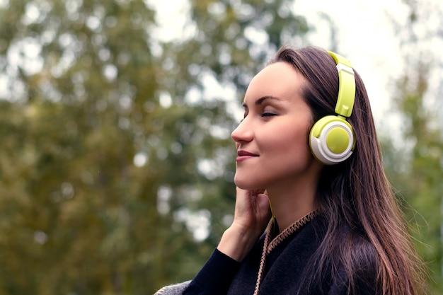 Jeune femme heureuse écoute de la musique de smartphone avec un casque dans un parc calme