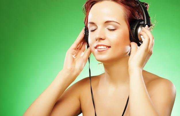 Jeune femme heureuse, écouter de la musique avec des casques