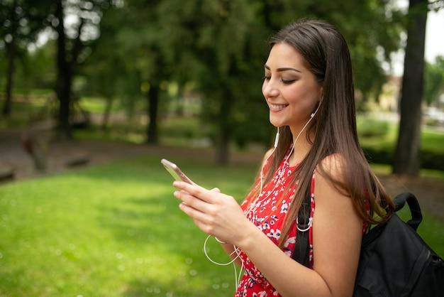 Jeune femme heureuse, écouter de la musique dans un parc