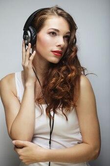 Jeune femme heureuse avec des écouteurs écoutant de la musique