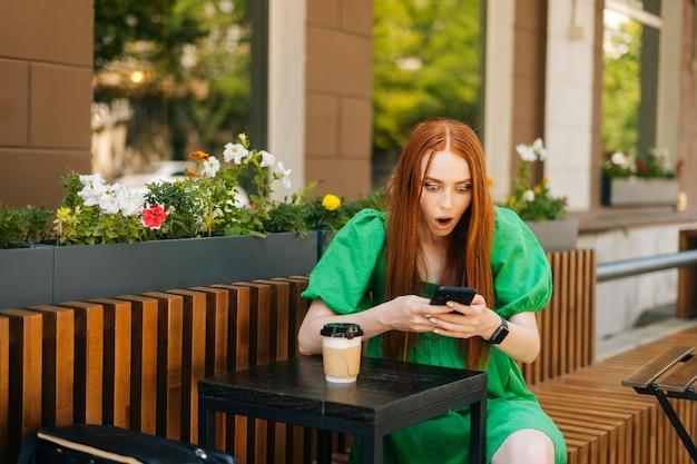 Jeune femme heureuse et excitée regardant l'écran du téléphone célébrant la victoire en ligne, assise à table avec une tasse de café sur la terrasse du café en plein air en journée ensoleillée d'été, arrière-plan flou, mise au point sélective.