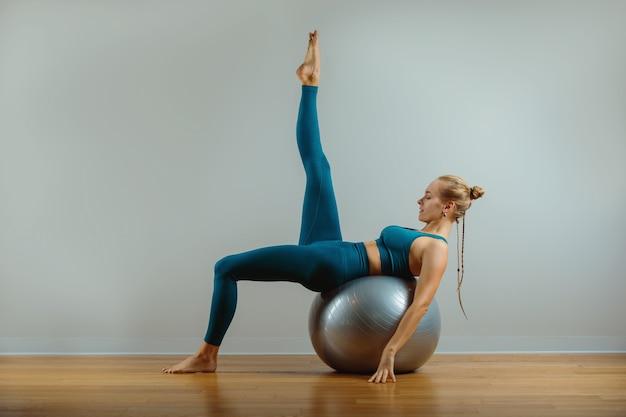 Jeune femme heureuse, faire des exercices de fitness avec ballon en forme à la maison.