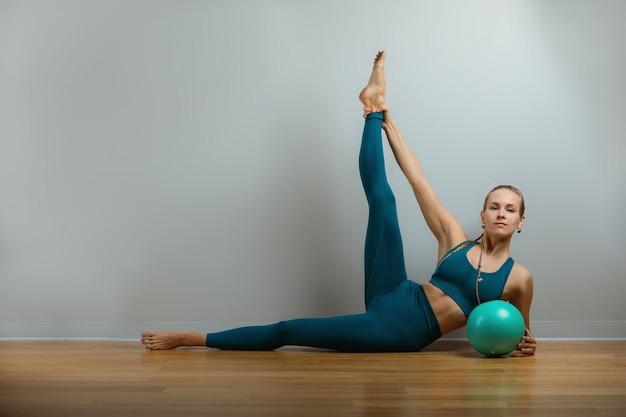 Jeune femme heureuse, faire des exercices de remise en forme avec ballon en forme à la maison corps mince rester à la maison formation indépendante