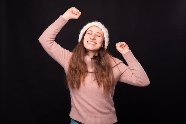 Jeune femme heureuse fait le geste gagnant sur fond noir.