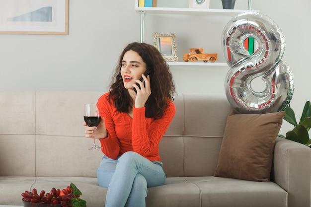 Jeune femme heureuse et heureuse en vêtements décontractés souriant joyeusement assise sur un canapé avec un verre de vin parlant au téléphone portable dans un salon lumineux célébrant la journée internationale de la femme le 8 mars