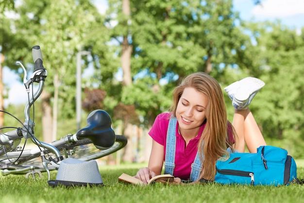 Jeune femme heureuse magnifique souriant tout en lisant un livre de détente sur l'herbe après le vélo au parc été printemps vacances loisirs bonheur littérature intelligence inspiration concept.