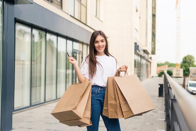 Jeune femme heureuse marchant avec des sacs à provisions à l'extérieur dans la rue