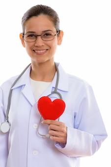 Jeune femme heureuse médecin souriant tout en tenant coeur rouge