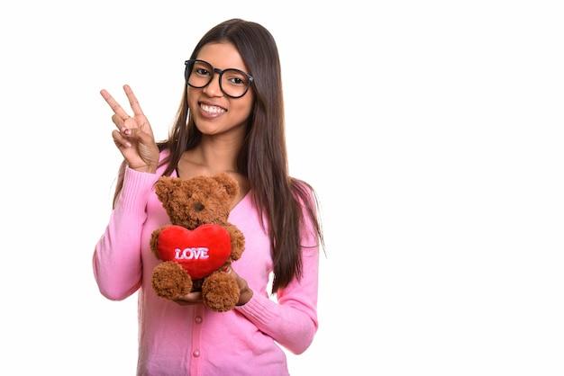 Jeune femme heureuse de nerd brésilien souriant et donnant signe de paix