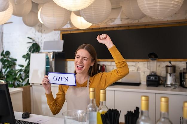 Une jeune femme heureuse d'ouvrir son café