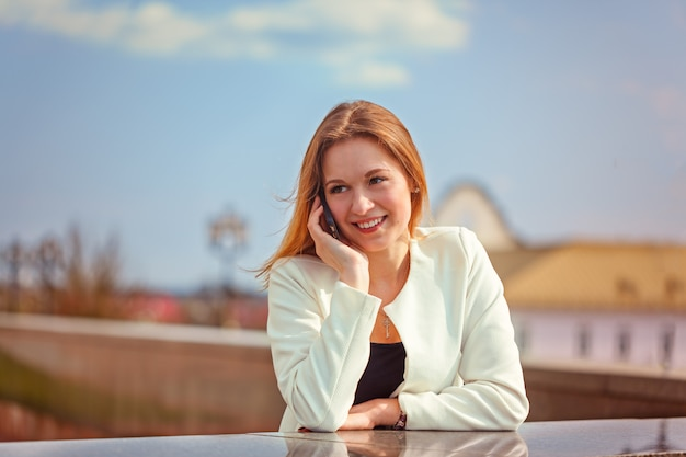 Jeune femme heureuse parle sur téléphone mobile