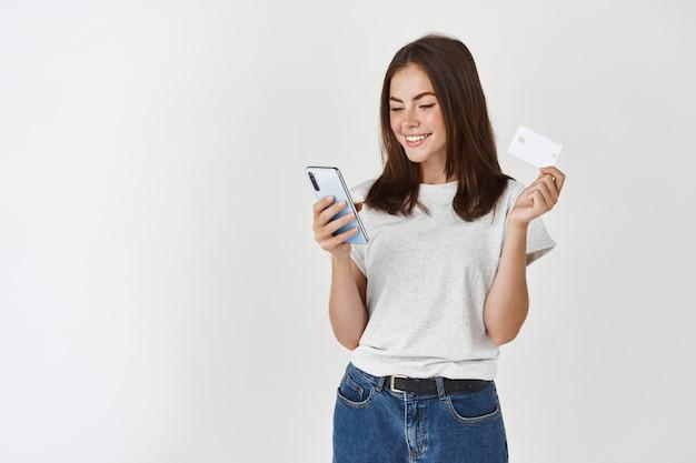 Jeune femme heureuse payant avec un smartphone et une carte de crédit en plastique, debout sur un mur blanc.