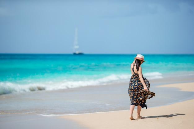 Jeune femme heureuse sur la plage blanche à pied