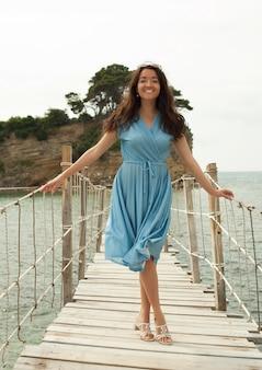 Jeune femme heureuse sur le pont près de la mer