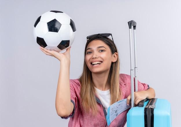 Une jeune femme heureuse portant une chemise rouge et des lunettes de soleil à la recherche tout en tenant le ballon avec des billets d'avion et une valise bleue sur un mur blanc