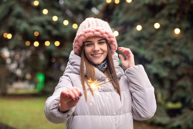 Une jeune femme heureuse porte un chapeau et un manteau tricotés roses s'amusant avec des cierges magiques dans la rue près de l'arbre de noël