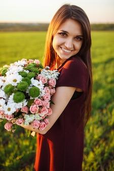 Jeune femme heureuse posant avec un gros bouquet, contre le coucher de soleil sur le terrain