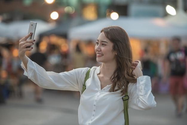 Jeune femme heureuse prenant selfie avec son smartphone au marché nocturne de shopping.