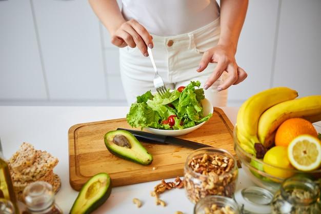 Jeune femme heureuse, préparer une savoureuse salade dans la belle cuisine avec des ingrédients frais verts à l'intérieur. alimentation saine et concept de régime. perdre du poids