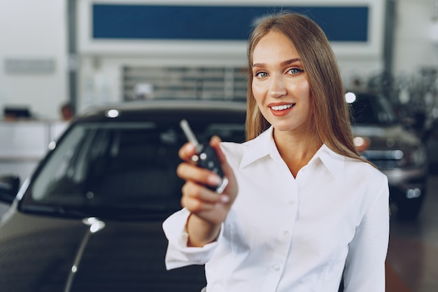 Jeune femme heureuse près de la voiture avec les clés en main