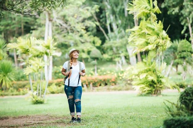 Jeune femme heureuse qui marche sur l'herbe verte avec sac à dos.