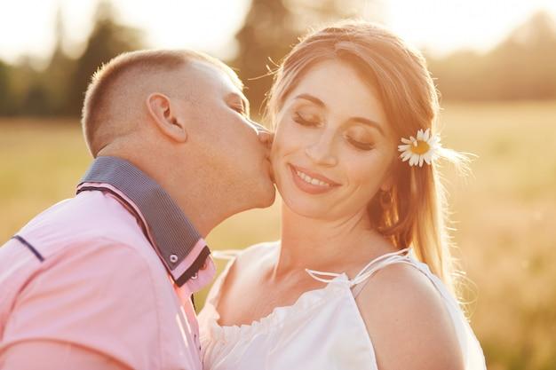 Une jeune femme heureuse reçoit le baiser de son petit ami, se promène en plein air à travers le champ, se montre l'amour. beau couple pose à l'extérieur ensemble. gens, relation amoureuse, concept de convivialité.