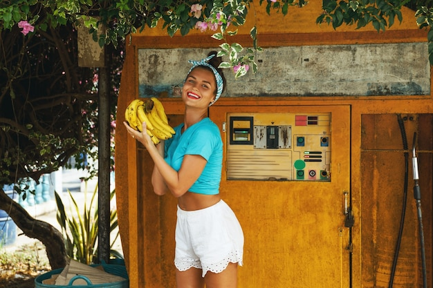 Jeune femme heureuse avec un régime de bananes posant à côté de la vieille station de remplissage