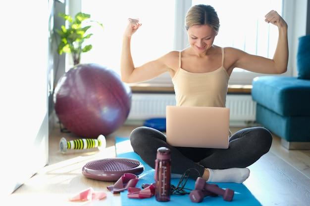 La jeune femme heureuse répète des exercices physiques regardez l'ordinateur portable