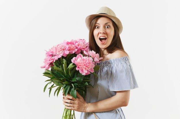 Jeune femme heureuse en robe bleue, chapeau tenant un bouquet de belles fleurs de pivoines roses isolées sur fond blanc. saint-valentin, concept de vacances de la journée internationale de la femme. espace publicitaire.