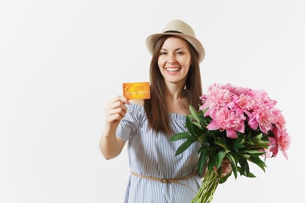 Jeune femme heureuse en robe bleue, chapeau tenant une carte bancaire de crédit, argent, bouquet de belles fleurs de pivoines roses isolées sur fond blanc. affaires, livraison, concept d'achat en ligne. espace de copie.