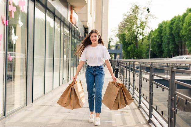Jeune femme heureuse avec des sacs à provisions marchant dans la rue.