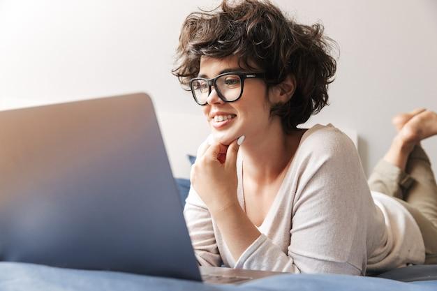 Une jeune femme heureuse se trouve à l'intérieur sur le lit à l'aide d'un ordinateur portable.
