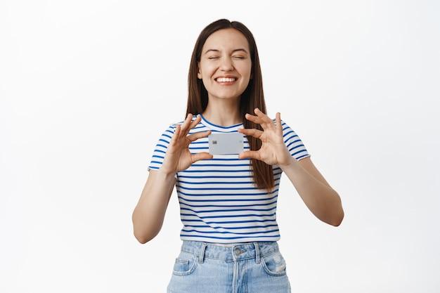 Une jeune femme heureuse se vante de sa nouvelle carte de crédit, se montre et sourit satisfaite, ferme les yeux, pense au shopping et aux remises, debout contre un mur blanc