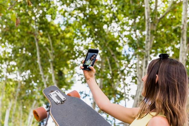 Jeune femme heureuse avec skateboard prenant selfie