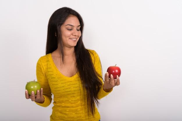 Jeune femme heureuse souriant tout en tenant la pomme verte et en regardant la pomme rouge