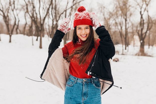 Jeune femme heureuse souriante assez candide dans des mitaines rouges et bonnet tricoté portant un manteau noir marchant jouant dans le parc dans la neige, des vêtements chauds, s'amuser